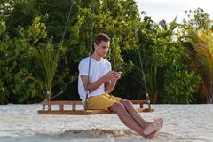 Young man seated on a swing and using his phone. White sand and jungle as background royalty free stock image