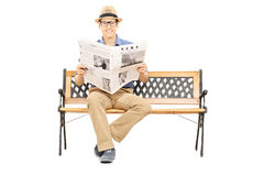 Young man seated on a wooden bench holding newspaper Royalty Free Stock Photos