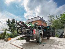 Young man securing two sports dirt bikes to the bed of the picku. P truck using blue safety belt or tie-down straps, in the residential setting Stock Photography