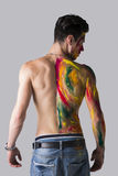 Young man seen from the back with skin painted with colors. Handsome young man seen from the back with skin all painted with holi colors Royalty Free Stock Image
