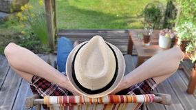 Young man  relaxing on a terrace in a garden. Young man seen back wearing a hat and relaxing on a terrace in a garden stock photo