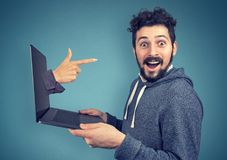 Young man selected as winnner. Excited young man holding laptop with hand choosing him smiling at camera Royalty Free Stock Images