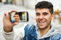Young man selfie in urban background with a smartphone Royalty Free Stock Photography