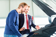 Young man and seller with auto in car dealership. Seller or car salesman and client or customer in car dealership presenting the engine performance of new and stock images