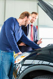 Young man and seller with auto in car dealership Royalty Free Stock Photography