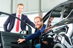 Young man and seller with auto in car dealership Royalty Free Stock Images