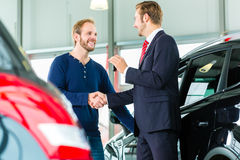 Young man and seller with auto in car dealership. Seller or car salesman and customer in auto dealership, they shaking hands, hands over the car keys and seal Stock Photos
