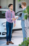 Young man and seller with auto in car dealership Royalty Free Stock Photo