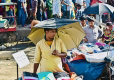 Young street seller is selling garments product in the road unique photo. A young man is selling various garments products around a footpath area in Bangladesh royalty free stock images