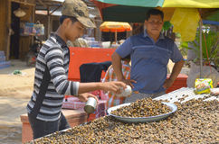 Young man sells fried snails Royalty Free Stock Images
