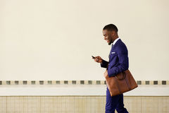 Young man sending text message on his mobile phone Stock Photography