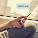 Young man sending a text message with the text wassuuuup Royalty Free Stock Images