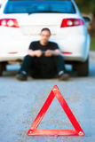 Young man sends an sms sitting by a white car Royalty Free Stock Photos