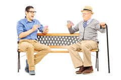 Young man and senior gentleman playing cards seated on a bench Royalty Free Stock Photos
