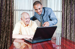Young Man and  Senior Male Working on Computer. Young African man standing behind and putting hand on shoulder of sitting, elderly Caucasian man and pointing at Royalty Free Stock Image
