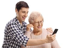 Young man and a senior woman listening to music on a smartphone royalty free stock image