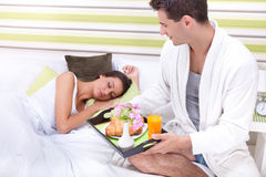 Young man serving breakfast for his girlfriend in bed. Portrait of happy young men serving breakfast for his girlfriend in bed at home Royalty Free Stock Photos