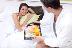 Young man serving breakfast for his girlfriend. Portrait of happy young men serving breakfast for his girlfriend in bed at home Royalty Free Stock Image