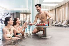 Young man serving with champagne two women at the swimming pool. Seductive young men serving with cold champagne and fresh sweet fruits two beautiful women at Royalty Free Stock Photography
