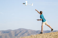 Young man setting remote control plane in air Stock Photos