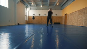 Young man shadow boxing coaches in the hall of MMA stock video
