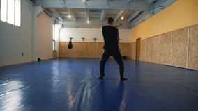 Young man shadow boxing coaches in the hall of MMA stock video footage