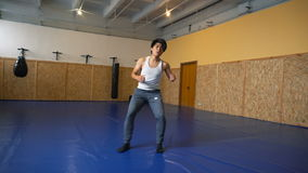 Young man shadow boxing coaches in the hall of MMA stock footage