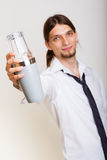 Young man with shaker making cocktail drink. Young stylish man bartender with shaker making alcohol cocktail drink studio shot on gray royalty free stock photos