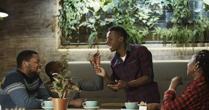 Young man sharing interesting story with friends. Group of cheerful African-American people listening to young men telling story expressively while chilling in Royalty Free Stock Photography