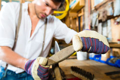Young man sharpening tools in mountains hut Royalty Free Stock Image