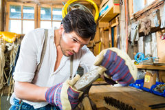 Young man sharpening tools in mountains hut Stock Photography