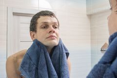 Young man shaved and washed himself wiping himself dry with a towel Royalty Free Stock Photos