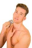 Young man shaves with electric razor Royalty Free Stock Image