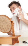 Young man shaves in the mirror Stock Photography