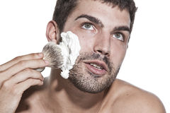 Young man shaving Stock Images
