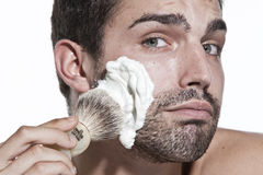 Young man shaving Royalty Free Stock Images