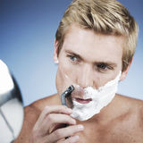 A young man shaving Royalty Free Stock Image