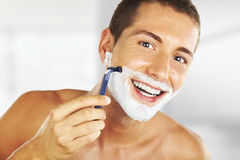 Young man shaving in the bath Stock Images