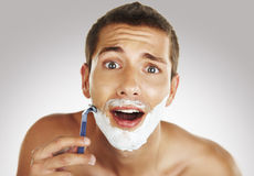 Young man shaving in the bath Stock Photo