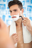 Young man shaving in the bath Stock Image