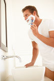 Young Man Shaving In Bathroom Mirror. SMiling Stock Photo