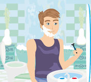Young man shaving in bathroom mirror Royalty Free Stock Photography