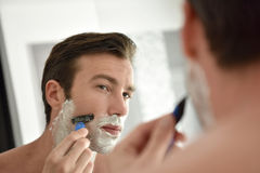 Young man shaving beard Royalty Free Stock Photo