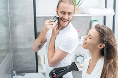 Young man shaving beard with electric razor and smiling woman drying hair with hair dryer. Handsome young men shaving beard with electric razor and smiling women stock photos