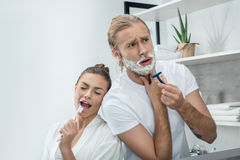 Young man shaving beard with razor while happy woman singing in toothbrush. Handsome young men shaving beard with razor while happy women singing in toothbrush royalty free stock images