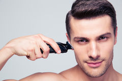 Young man shaving with electric razor Stock Photos