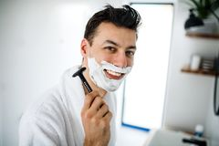 Young man with shaving foam in the bathroom in the morning, daily routine. Young man with shaving foam on face in the bathroom in the morning, a daily routine stock photo