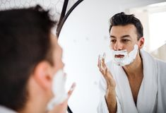 Young man with shaving foam in the bathroom in the morning, daily routine. Young man with shaving foam on face in the bathroom in the morning, a daily routine stock image