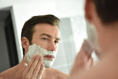 Young man shaving  in front of the mirror Royalty Free Stock Photo