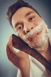 Young man shaving having fun with machete. Stock Image